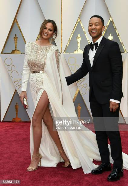 John Legend and US model and wife of John Legend Chrissy Teigen arrive on the red carpet for the 89th Oscars on February 26 2017 in Hollywood...