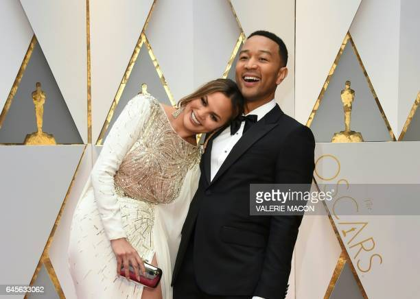 TOPSHOT John Legend and US model and wife of John Legend Chrissy Teigen arrive on the red carpet for the 89th Oscars on February 26 2017 in Hollywood...