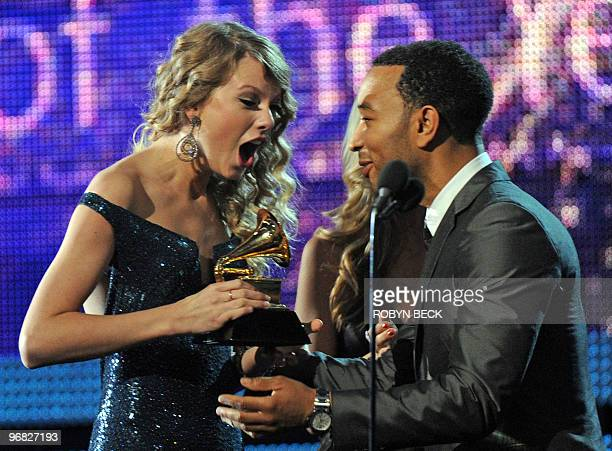 John Legend presents to Taylor Swift the award for the Best Album of the Year during the 52nd annual Grammy Awards in Los Angeles California on...
