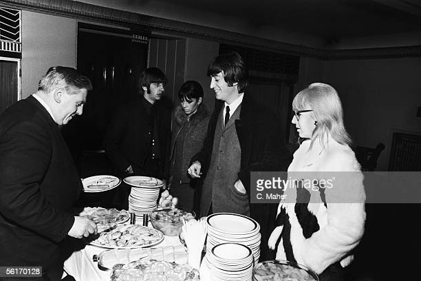 John Lennon and Ringo Starr of the Beatles queue for food in the bar of the Saville Theatre in London after an Arts Theatre premiere 17th February...