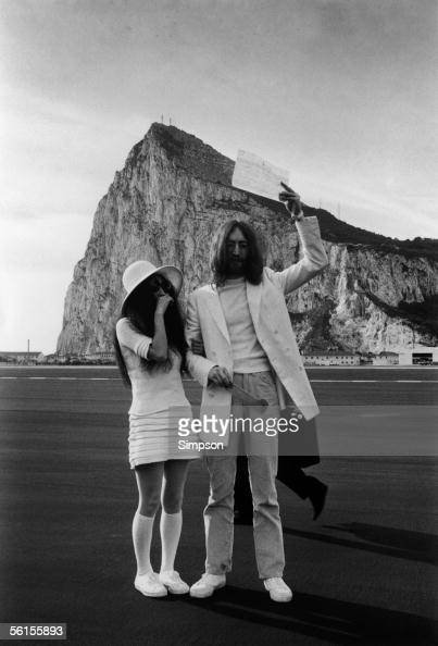 John Lennon and Yoko Ono both dressed in white with their marriage certificate after their wedding in Gibraltar 20th March 1969