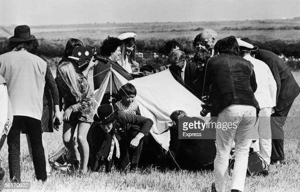 John Lennon of the Beatles emerges from a tent during the location filming of 'Magical Mystery Tour' 16th September 1967 George Harrison stands to...