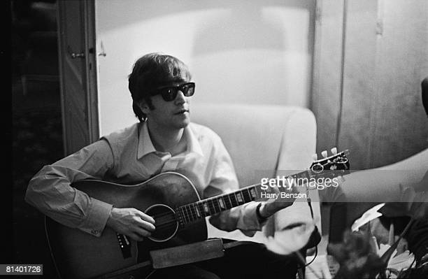 John Lennon of the Beatles plays the guitar in a hotel room in Paris 16th January 1964