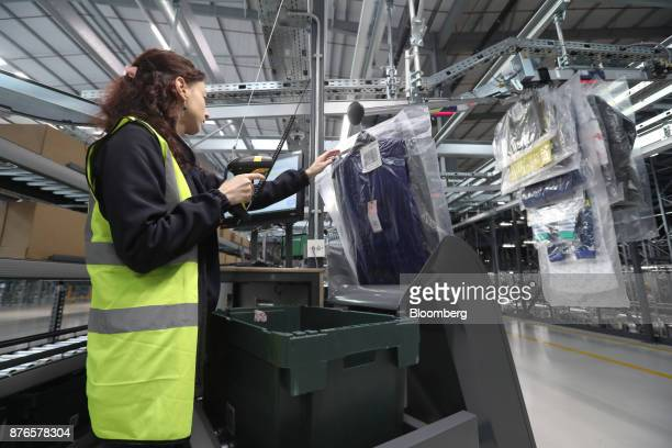 A John Lewis Plc partner scans and packs hanging garments at the John Lewis Plc customer fulfilment and distribution centre in Milton Keynes UK on...