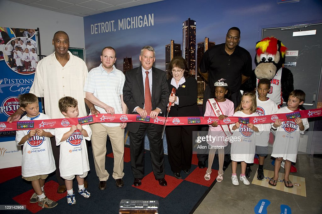 John Long, former Detroit Piston player, Lawrence Frank, Detroit Pistons Head Coach, Ric DeVore, PNC Bank President, Julie Johnson, Children's Museum Director, Rick Mahorn, former Detroit Piston player, and Hooper, the Pistons' mascot participate in the ribbon-cutting ceremony at the Detroit Children's Museum as part of the 25th Pistons Live, Learn, and Play Center renovation on August 31, 2011 in Detroit, Michigan.