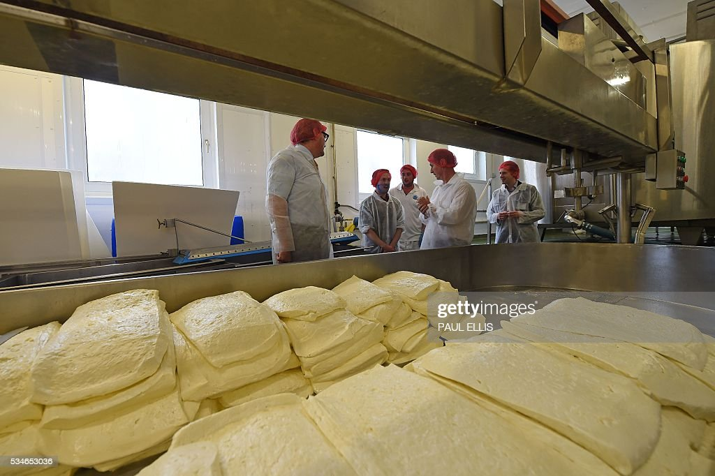 John Longworth, former Director-General of the British Chambers of Commerce, and current Chairman of the 'Vote Leave' Business Council (L), the official 'Leave' campaign organisation for the forthcoming EU referendum, talks with employees as he tours Singleton's Dairy in Preston, north-west England, on May 27, 2016. Campaigners for a 'Leave' vote in Britain's EU referendum launched an online competition and poll Friday offering £50 million for anyone who correctly predicts the outcome of every Euro 2016 fixture. The Vote Leave campaign said it had chosen the prize amount for the European football championships because it was equivalent to the sum that Britain contributes to the European Union budget every day. / AFP / PAUL
