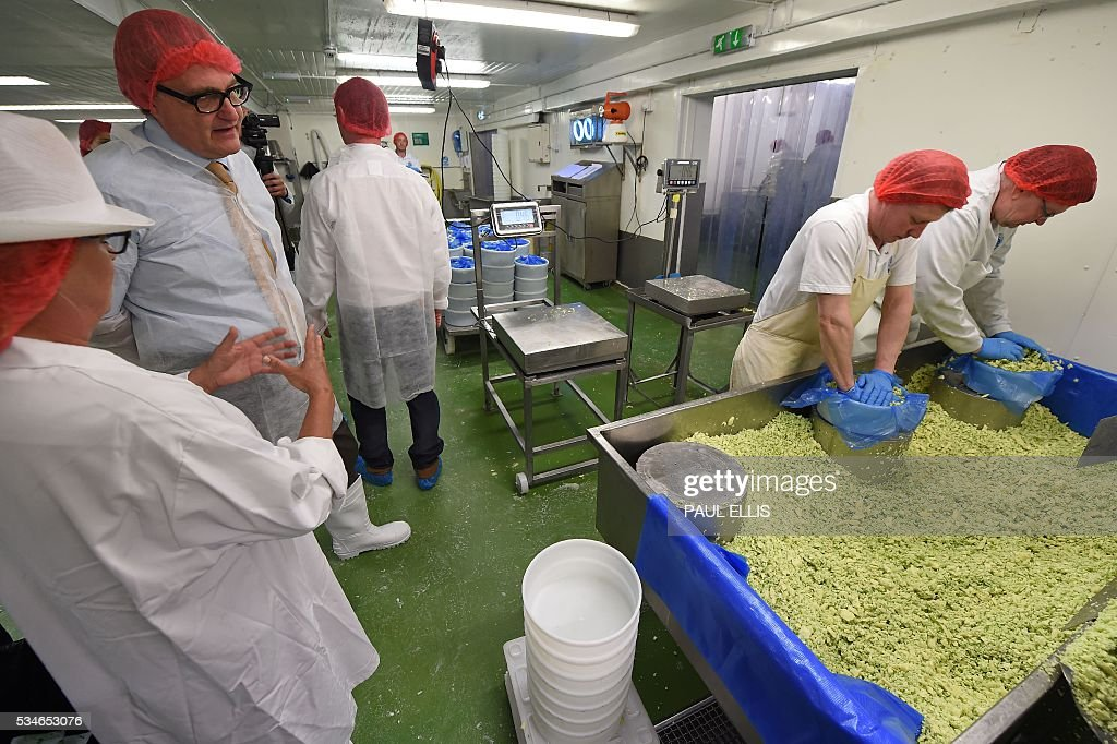 John Longworth, former Director-General of the British Chambers of Commerce, and current Chairman of the 'Vote Leave' Business Council (2L), the official 'Leave' campaign organisation for the forthcoming EU referendum, talks with employees as he tours Singleton's Dairy in Preston, north-west England, on May 27, 2016. Campaigners for a 'Leave' vote in Britain's EU referendum launched an online competition and poll Friday offering £50 million for anyone who correctly predicts the outcome of every Euro 2016 fixture. The Vote Leave campaign said it had chosen the prize amount for the European football championships because it was equivalent to the sum that Britain contributes to the European Union budget every day. / AFP / PAUL