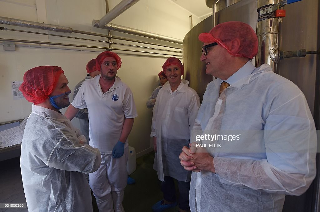 John Longworth, former Director-General of the British Chambers of Commerce, and current Chairman of the 'Vote Leave' Business Council, the official 'Leave' campaign organisation for the forthcoming EU referendum (R), meets employees during his tour of Singleton's Dairy in Preston, north-west England, on May 27, 2016. Campaigners for a 'Leave' vote in Britain's EU referendum launched an online competition and poll Friday offering £50 million for anyone who correctly predicts the outcome of every Euro 2016 fixture. The Vote Leave campaign said it had chosen the prize amount for the European football championships because it was equivalent to the sum that Britain contributes to the European Union budget every day. / AFP / PAUL