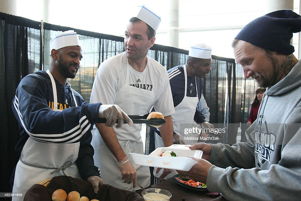 John Lucas III #5 and Michael Sanders Assistant Coach of the Utah Jazz dish out food during the we care-we share Thanksgiving Dinner feeding the homeless at EnergySolutions Arena on November 27, 2013 in Salt Lake City, Utah.