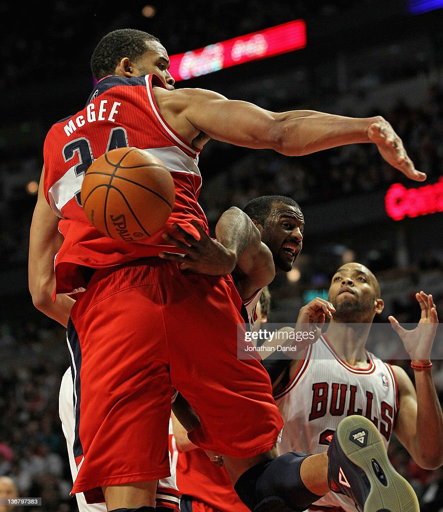 John Lucas III of the Chicago Bulls passes the ball behind the back of JaVale McGee of the Washington Wizards at the United Center on January 11 2012...