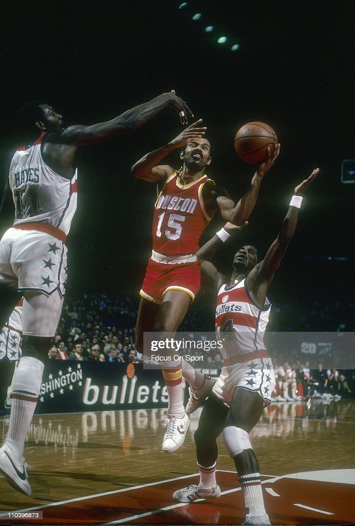 John Lucas of the Houston Rockets shoots between Elvin Hayes and Tom Henderson of the Washington Bullets during an NBA basketball game circa 1977 at...