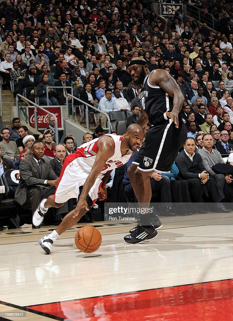 John Lucas #5 of the Toronto Raptors drives against Reggie Evans #30 of the Brooklyn Nets on December 12, 2012 at the Air Canada Centre in Toronto, Ontario, Canada.