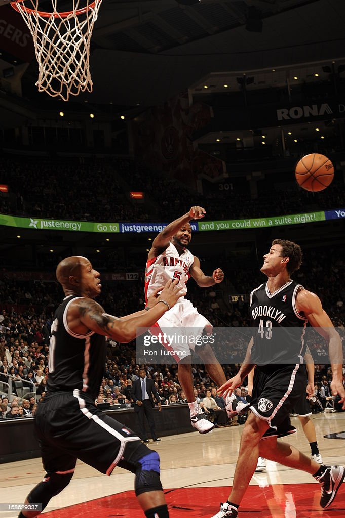 John Lucas #5 of the Toronto Raptors passes the ball against Keith Bogans #10 and Kris Humphries #43 of the Brooklyn Nets on December 12, 2012 at the Air Canada Centre in Toronto, Ontario, Canada.
