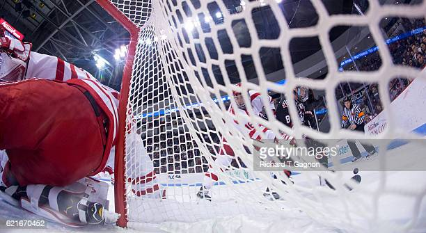 John MacLeod of the Boston University Terriers battles for the puck against Adam Gaudette of the Northeastern Huskies behind the net during NCAA...