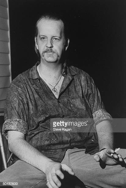 John Mark Byers father of murder victim Christopher Byers holding lit cigarette as he sits in chair at home Christopher's ravaged body along w that...