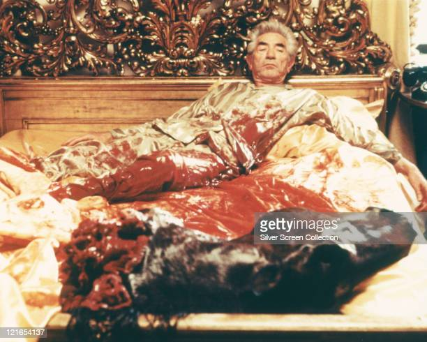 John Marley US actor wearing striped pyjamas in bed with bloodstained bedclothes and the severed head of his horse at the foot of the bed in a...