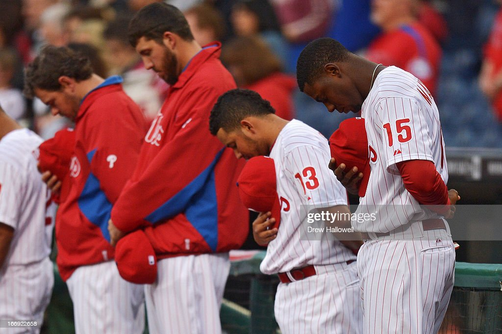 John Mayberry Jr. #15, Freddy Galvis #13 and the Philadelphia Phillies observe a moment of silence for the victims of the Boston Marathon bombing before the game against the St. Louis Cardinals at Citizens Bank Park on April 18, 2013 in Philadelphia, Pennsylvania.
