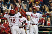 John Mayberry Jr #15 of the Philadelphia Phillies cheers for teammate Michael Martinez as he crosses home for the game winning run on a Ryan Howard...