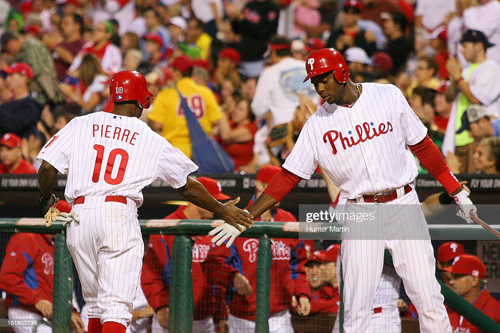 John Mayberry Jr. #15 of the Philadelphia Phillies congratulates Juan Pierre #10 after scoring a run during a game against the Miami Marlins at Citizens Bank Park on September 11, 2012 in Philadelphia, Pennsylvania.