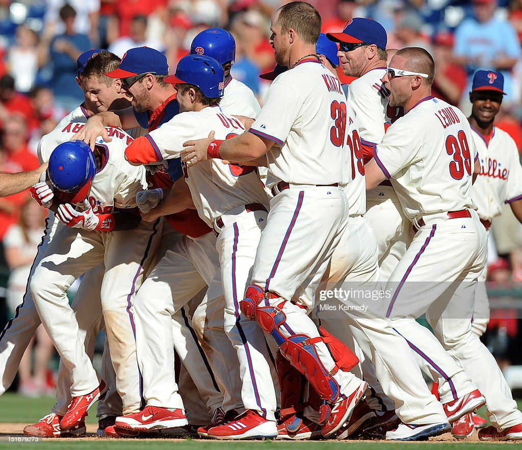 John Mayberry Jr. #15 of the Philadelphia Phillies is congratulated by teammates after hitting a walk off single against the Colorado Rockies during the ninth inning on September 9, 2012 at Citizens Bank Park in Philadelphia, Pennsylvania. The Phillies won 3-2.