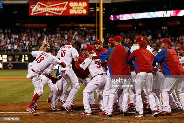 John Mayberry Jr #15 of the Philadelphia Phillies is met at the plate after hitting a Grand Slam Home Run in the 11th inning to win game against the...