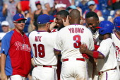 John Mayberry Jr #15 of the Philadelphia Phillies is mobbed by teammates after singling in the winning run in the 10th inning during a game against...