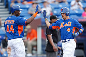 John Mayberry Jr #44 and Wilmer Flores of the New York Mets celebrate after scoring on a double by Bobby Parnell against the Atlanta Braves in the...