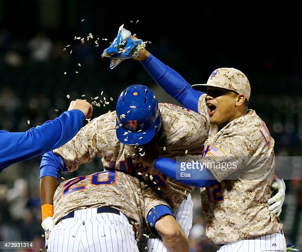 John Mayberry Jr #44 of the New York Mets is congratulated by teamamtes Anthony Recker and Juan Lagares after Mayberry Jr drove in the game winning...