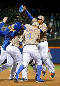 John Mayberry Jr #44 of the New York Mets is surrounded by teammates after he drove in the game winning run to defeat the St Louis Cardinals 21 in...