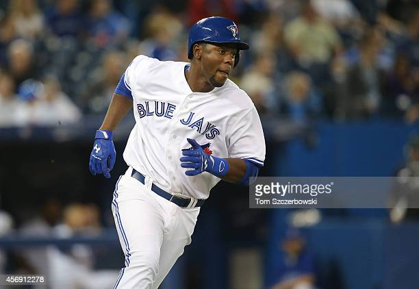 John Mayberry Jr #9 of the Toronto Blue Jays runs to first base as he hits a double in the eighth inning during MLB game action against the Chicago...