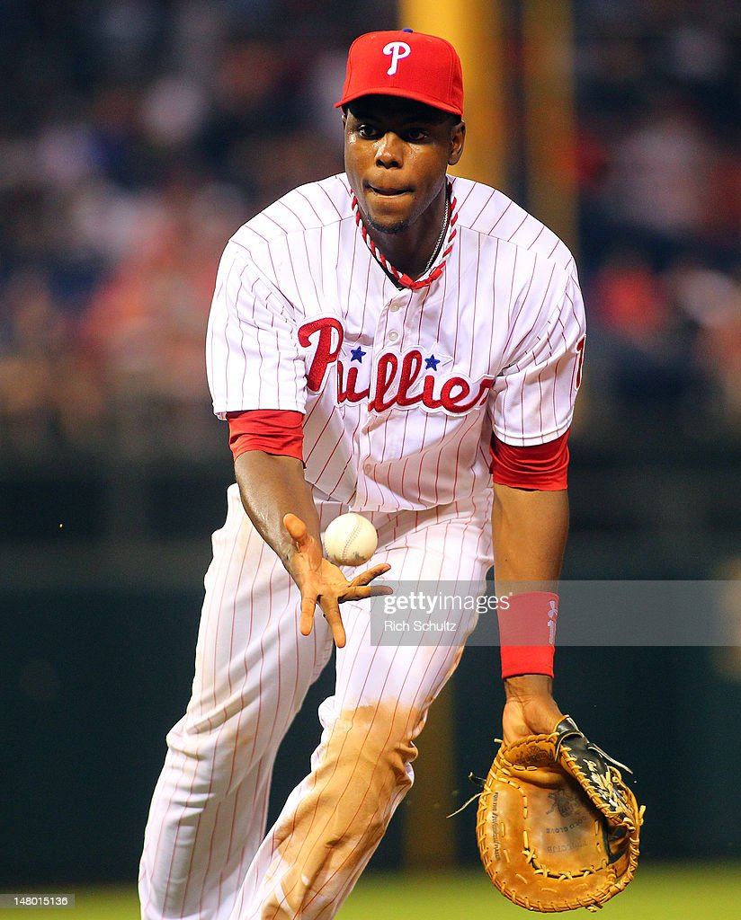 John Mayberry #15 of the Philadelphia Phillies flips the ball to pitcher Jake Diekman (not pictured) for the out against the Atlanta Braves during a MLB baseball game on July 7, 2012 at Citizens Bank Park in Philadelphia, Pennsylvania. The Braves defeated the Phillies 6-3.
