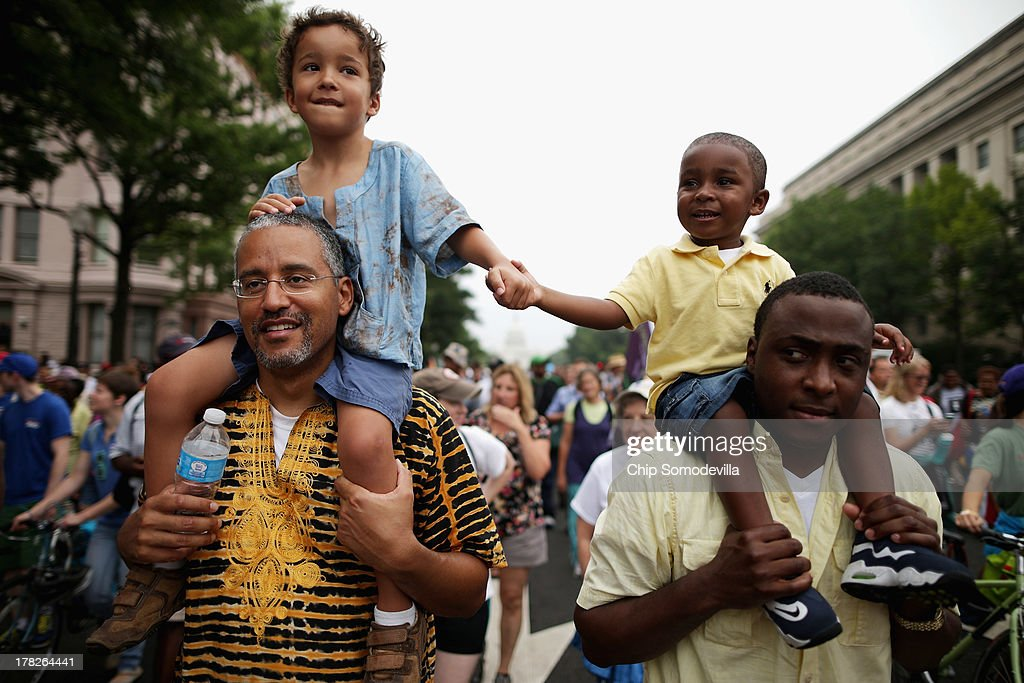 John Mbugua and his son Giovanni Mbugua, 6, of San Jose, California, and Lavon Johnson and his son Mason Johnson, 2, of Fort Meade Maryland, hold hands while marching with thousands of other people from Capitol Hill to the Lincoln Memorial during the 'Let Freedom Ring Commemoration and Call to Action' honoring the 50th anniversary of the historic March on Washington for Jobs and Freedom August 28, 2013 in Washington, DC. The 1963 landmark civil rights event was where Dr. Martin Luther King Jr. delivered his famous speech, saying, 'I still have a dream, a dream deeply rooted in the American dream...one day this nation will rise up and live up to its creed, 'We hold these truths to be self evident: that all men are created equal.' I have a dream . . .'