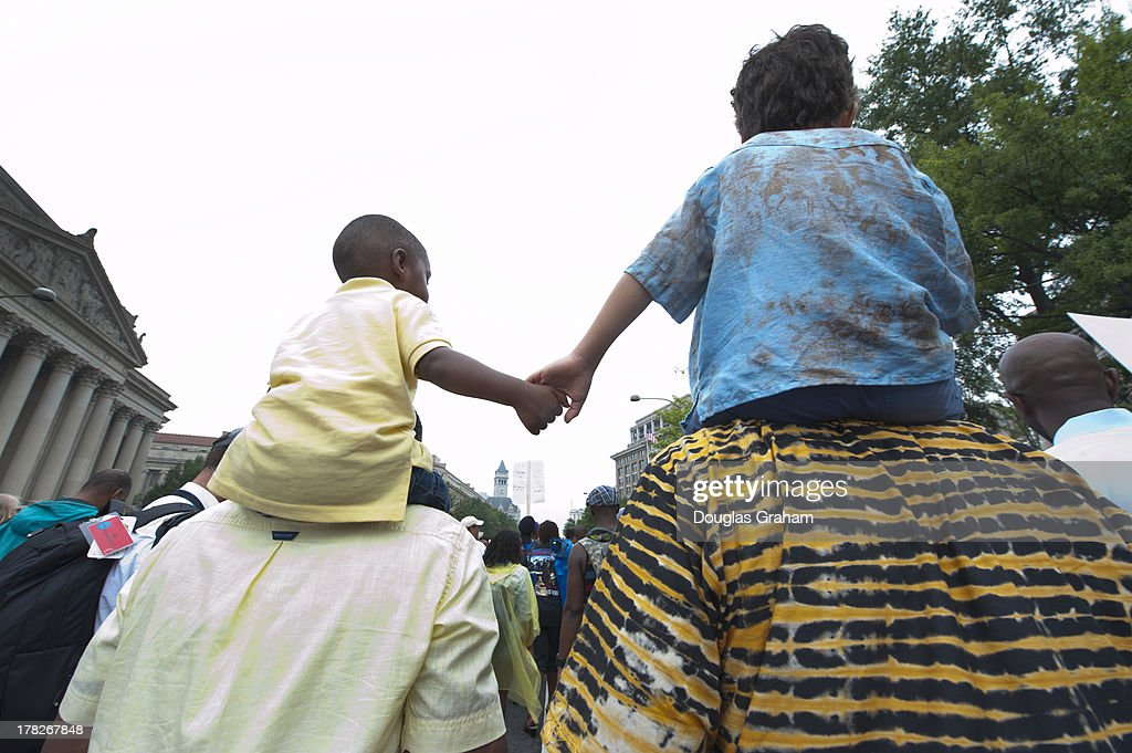 John Mbugua and his son Giovanni Mbugua, 6, of San Jose, California, and (L)Lavon Johnson and his son Mason Johnson, 2, of Fort Meade Maryland, hold hands while marching with thousands of citizens from Capitol Hill to the Lincoln Memorial during the 'Let Freedom Ring Commemoration and Call to Action' honoring the 50th anniversary of the historic March on Washington for Jobs and Freedom August 28, 2013 in Washington, DC. The 1963 landmark civil rights event was where Dr. Martin Luther King Jr. delivered his famous speech from the Lincoln Memorial.