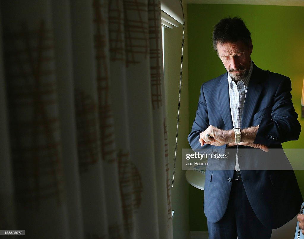 <a gi-track='captionPersonalityLinkClicked' href=/galleries/search?phrase=John+McAfee&family=editorial&specificpeople=1353446 ng-click='$event.stopPropagation()'>John McAfee</a> checks his watch in his room at the Beacon Hotel where he is staying after arriving last night from Guatemala on December 13, 2012 in Miami Beach, Florida. McAfee is a 'person of interest' in the fatal shooting of his neighbor in Belize and turned up in Guatemala after a month on the run in Belize.