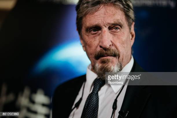 John McAfee founder of McAfee Associates Inc and chief cybersecurity visionary at MGTCapital Investments Inc listens during a Bloomberg Television...