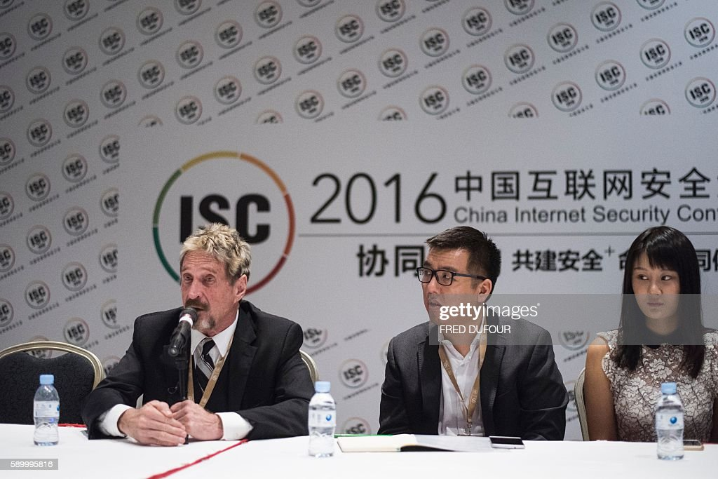 John McAfee founder of the eponymous antivirus company and Chinese translators speaks to journalists at the China Internet Security Conference in...