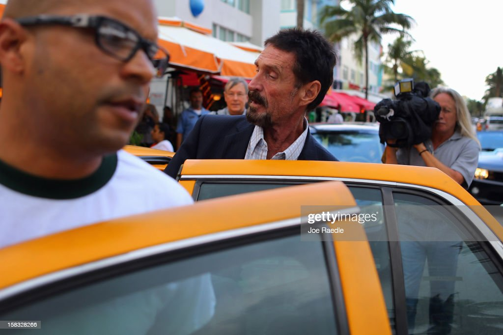 John McAfee (C) gets into a cab in front of the Beacon Hotel where he is staying after arriving last night from Guatemala on December 13, 2012 in Miami Beach, Florida. McAfee is a 'person of interest' in the fatal shooting of his neighbor in Belize and turned up in Guatemala after a month on the run in Belize.