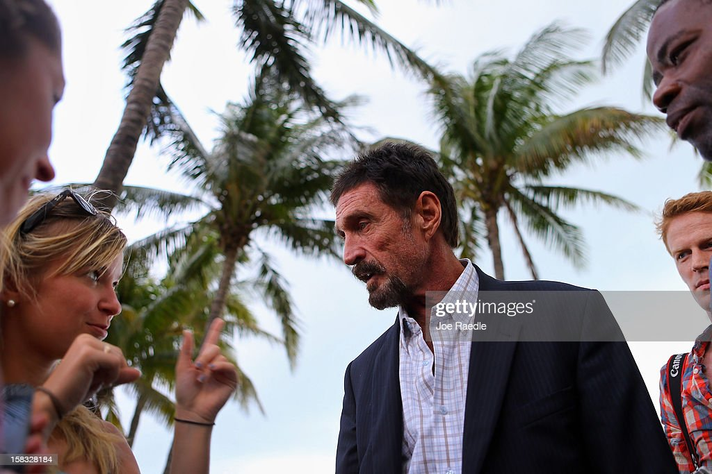 <a gi-track='captionPersonalityLinkClicked' href=/galleries/search?phrase=John+McAfee&family=editorial&specificpeople=1353446 ng-click='$event.stopPropagation()'>John McAfee</a> interacts with people after speaking to reporters outside of the Beacon Hotel where he is staying after arriving last night from Guatemala on December 13, 2012 in Miami Beach, Florida. McAfee is a 'person of interest' in the fatal shooting of his neighbor in Belize and turned up in Guatemala after a month on the run in Belize.