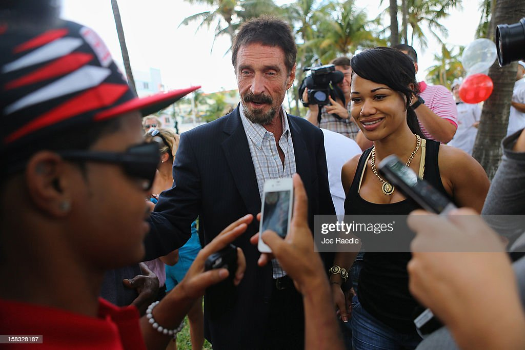 <a gi-track='captionPersonalityLinkClicked' href=/galleries/search?phrase=John+McAfee&family=editorial&specificpeople=1353446 ng-click='$event.stopPropagation()'>John McAfee</a> (C) interacts with people after speaking to reporters outside of the Beacon Hotel where he is staying after arriving last night from Guatemala on December 13, 2012 in Miami Beach, Florida. McAfee is a 'person of interest' in the fatal shooting of his neighbor in Belize and turned up in Guatemala after a month on the run in Belize.