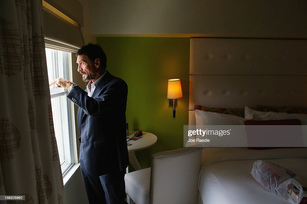 John McAfee looks out the window of his room at the Beacon Hotel where he is staying after arriving last night from Guatemala on December 13, 2012 in Miami Beach, Florida. McAfee is a 'person of interest' in the fatal shooting of his neighbor in Belize and turned up in Guatemala after a month on the run in Belize.