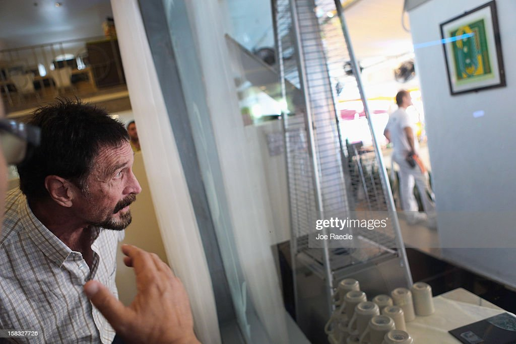 <a gi-track='captionPersonalityLinkClicked' href=/galleries/search?phrase=John+McAfee&family=editorial&specificpeople=1353446 ng-click='$event.stopPropagation()'>John McAfee</a> looks out the window of the lobby at the Beacon Hotel where he is staying after arriving last night from Guatemala on December 13, 2012 in Miami Beach, Florida. McAfee is a 'person of interest' in the fatal shooting of his neighbor in Belize and turned up in Guatemala after a month on the run in Belize.