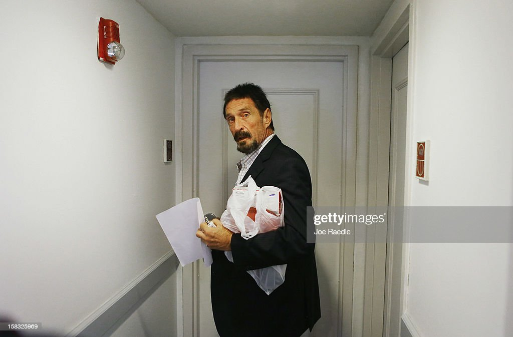 <a gi-track='captionPersonalityLinkClicked' href=/galleries/search?phrase=John+McAfee&family=editorial&specificpeople=1353446 ng-click='$event.stopPropagation()'>John McAfee</a> prepares to enter his room at the Beacon Hotel where he is staying after arriving last night from Guatemala on December 13, 2012 in Miami Beach, Florida. McAfee is a 'person of interest' in the fatal shooting of his neighbor in Belize and turned up in Guatemala after a month on the run in Belize.