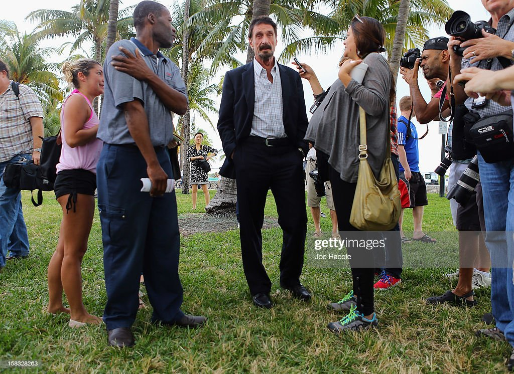 John McAfee (C) speaks with people outside of the Beacon Hotel where he is staying after arriving last night from Guatemala on December 13, 2012 in Miami Beach, Florida. McAfee is a 'person of interest' in the fatal shooting of his neighbor in Belize and turned up in Guatemala after a month on the run in Belize.