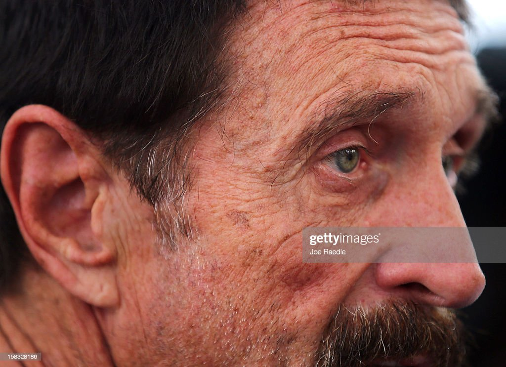 John McAfee speaks with reporters outside of the Beacon Hotel where he is staying after arriving last night from Guatemala on December 13, 2012 in Miami Beach, Florida. McAfee is a 'person of interest' in the fatal shooting of his neighbor in Belize and turned up in Guatemala after a month on the run in Belize.
