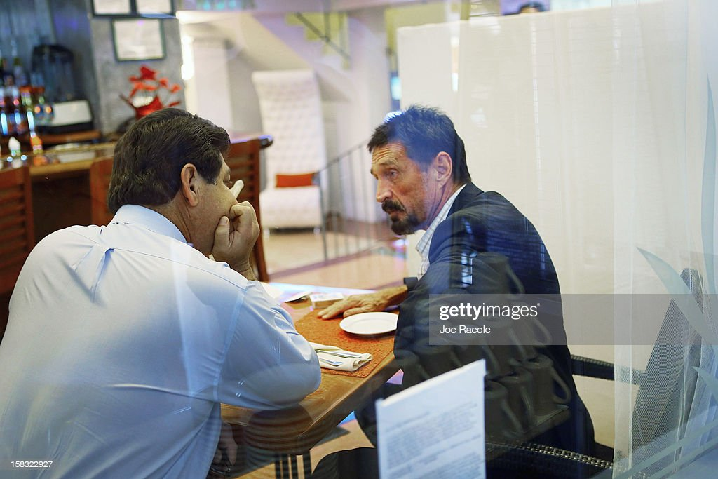 John McAfee (R) talks to a member of the media as he sits down for breakfast at the Beacon Hotel where he is staying after arriving last night from Guatemala on December 13, 2012 in Miami Beach, Florida. McAfee is a 'person of interest' in the fatal shooting of his neighbor in Belize and turned up in Guatemala after a month on the run in Belize.