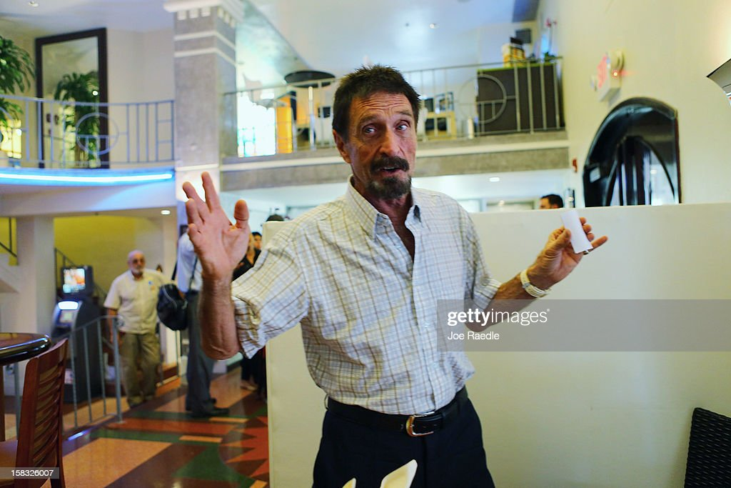 John McAfee talks to the media at the Beacon Hotel where he is staying after arriving last night from Guatemala on December 13, 2012 in Miami Beach, Florida. McAfee is a 'person of interest' in the fatal shooting of his neighbor in Belize and turned up in Guatemala after a month on the run in Belize.