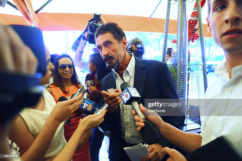 John McAfee talks to the media outside Beacon Hotel where he is staying after arriving last night from Guatemala on December 13, 2012 in Miami Beach, Florida. McAfee is a 'person of interest' in the fatal shooting of his neighbor in Belize and turned up in Guatemala after a month on the run in Belize.