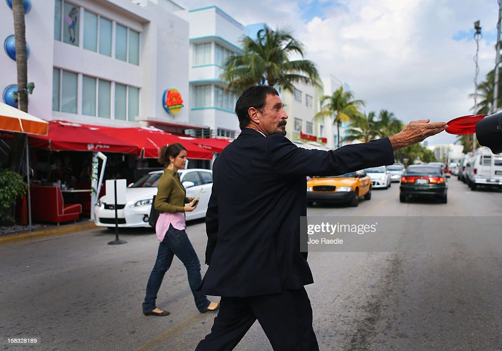 John McAfee tosses a frisbee to reporters as he walks out of the Beacon Hotel where he is staying after arriving last night from Guatemala on December 13, 2012 in Miami Beach, Florida. McAfee is a 'person of interest' in the fatal shooting of his neighbor in Belize and turned up in Guatemala after a month on the run in Belize.