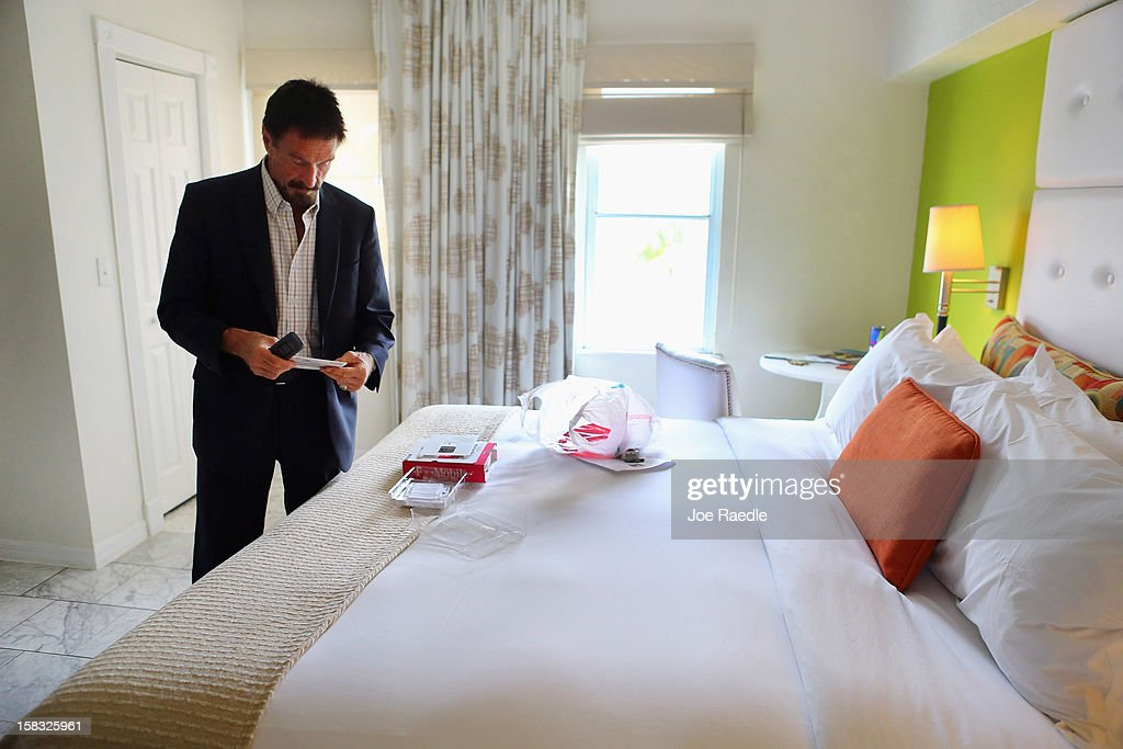 John McAfee unpacks a new cell phone in his room at the Beacon Hotel where he is staying after arriving last night from Guatemala on December 13, 2012 in Miami Beach, Florida. McAfee is a 'person of interest' in the fatal shooting of his neighbor in Belize and turned up in Guatemala after a month on the run in Belize.
