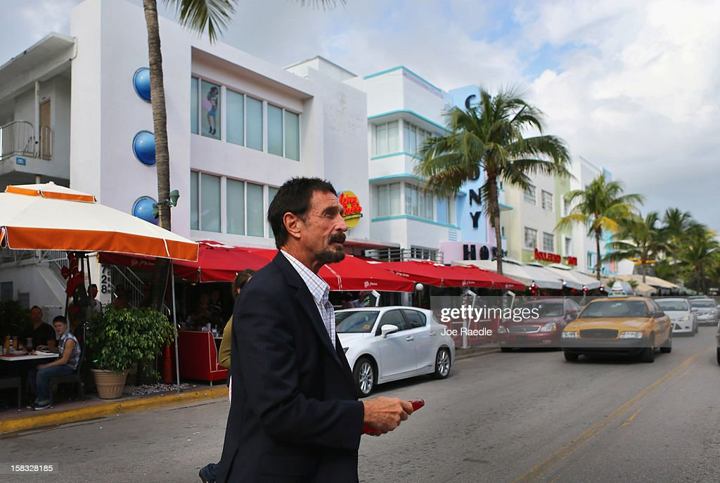 <a gi-track='captionPersonalityLinkClicked' href=/galleries/search?phrase=John+McAfee&family=editorial&specificpeople=1353446 ng-click='$event.stopPropagation()'>John McAfee</a> walks out of the Beacon Hotel where he is staying after arriving last night from Guatemala on December 13, 2012 in Miami Beach, Florida. McAfee is a 'person of interest' in the fatal shooting of his neighbor in Belize and turned up in Guatemala after a month on the run in Belize.